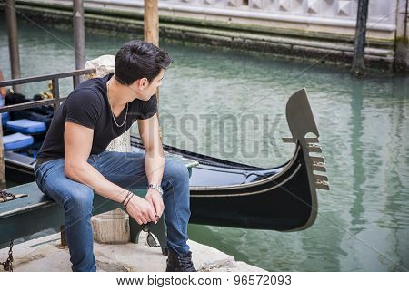 Young Man Sitting Next to Canal in Venice, Italy