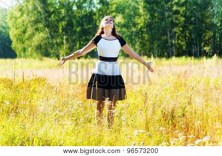 Girl outdoor in the meadow field enjoying nature