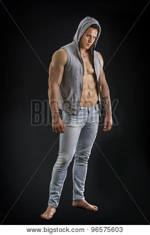 Confident, attractive young man with open vest on muscular torso