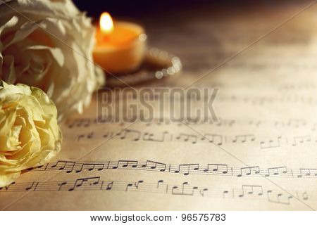Beautiful roses with pearls and candle on music sheets background