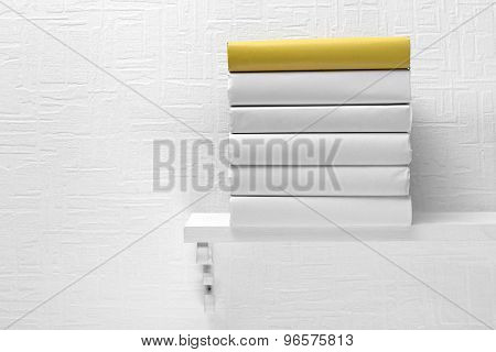Blank books and yellow one on shelf on white wallpaper background