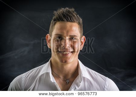 Headshot of smiling attractive young man in white shirt