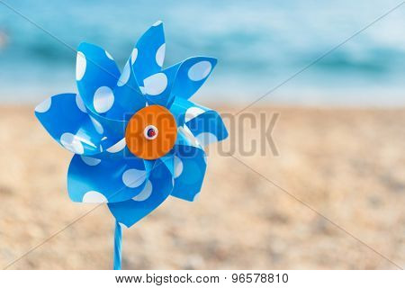 Blue and white windmill toy at the beach