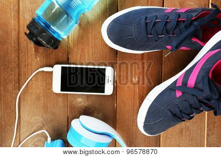 Sport shoes with bottle of water and headphones on wooden background