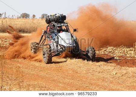Custom Single Seater Rally Buggy Kicking Up Trail Of Dust On Sand Track During Rally Race.