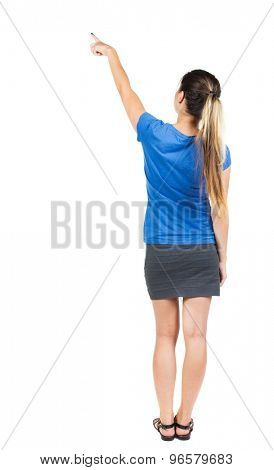 Back view pointing woman. beautiful girl. Rear view people collection.  backside view person. Isolated over white background. Girl in a gray skirt and blue T-shirt shows a finger of his right hand up.