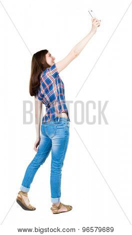 back view standing young beautiful woman and using a mobile phone. girl  watching. Isolated over white background. young girl in checkered blue with red stripes is photographed raising high over phone