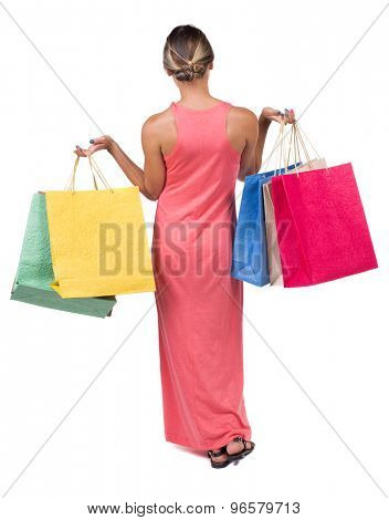 back view going woman in dress woman with shopping bags . beautiful brunette girl in motion.  Isolated over white background. girl in light red dress standing holding a raised hand with shopping bags