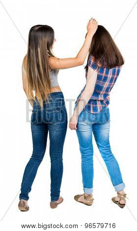 Back view of two young woman. Rear view people collection.  backside view of person. Rear view. Isolated over white background. She straightens her hair her friend.