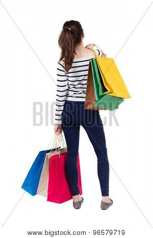 back view of going  woman woman with shopping bags. beautiful brunette girl in motion.  Isolated over white background. Frenchwoman in vest standing with lots of shopping bags.