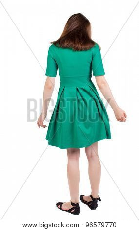 back view of young beautiful girl standing in thoughtful pose. Rear view people collection.    Isolated over white background. The girl in stylish green dress standing and looking in front of him.