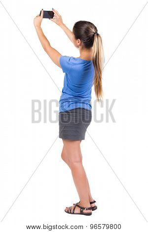 back view standing young beautiful  woman  in vest and using a mobile phone. girl  watching. Isolated over white background. Girl in a gray skirt and blue shirt photographing something at top of phone