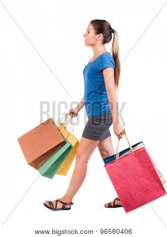 back view of going  woman  with shopping bags . beautiful girl in motion.  backside view of person.   Isolated over white background. Girl in a gray skirt and blue T-shirt carries shopping bags.