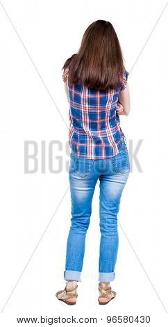 back view of standing young beautiful  woman.  girl  watching. Rear view people collection.  backside view of person.  A young girl in a checkered blue with red stripes is folded arms from the cold.