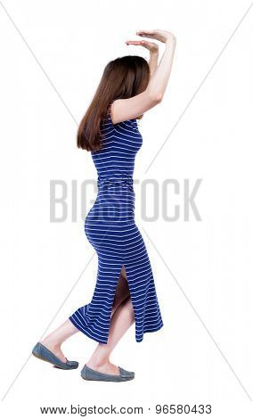 back view of woman  protects hands from what is falling from above. Man holding a heavy load backside view of person. Isolated over white background. Girl in a blue striped dress holding top heaviness