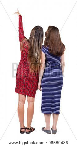 Back view of two pointing young girl. Rear view people collection.  backside view of person. Rear view. Isolated over white background. Two girls in dresses showing a thumbs up to the left.