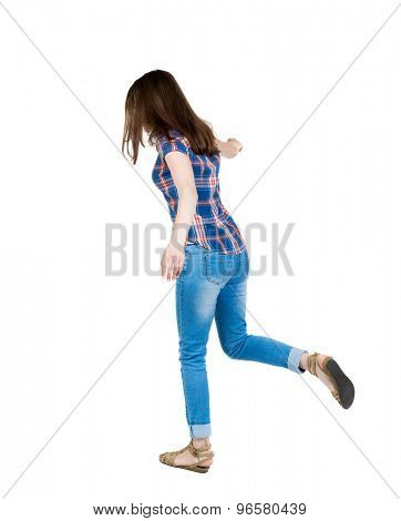 Back view woman Balances waving his arms.   Standing young girl in jeans. Rear view people collection.  backside view of person. A young girl in a checkered blue with red stripes on right foot jumps.