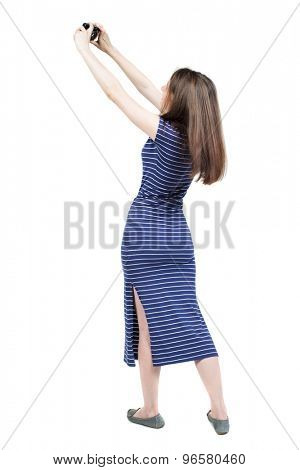 Back view of woman photographing.   girl photographer in dress. Rear view people collection.  Isolated over white background. Girl in a blue striped dress is photographed on a compact camera.