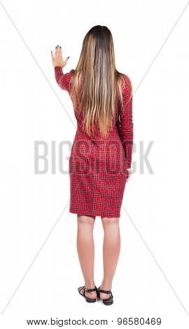 back view of young woman presses down on something. Isolated over white background. backside view of person. Long-haired girl in a red plaid dress presses the right hand at something in front of him.