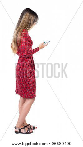 back view of standing young beautiful  woman  in vest and using a mobile phone. girl  watching.  Isolated over white background. Long-haired girl in a red plaid dress holding a phone in his right hand