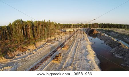 RUSSIA, VOSKRESENSK - JUL 1, 2014: Sandpit with bulldozers and excavator near forest during sunset. Aerial view. Photo with noise from action camera.