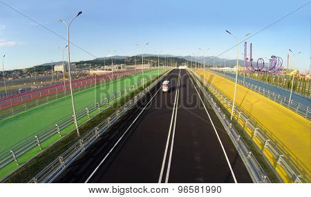 RUSSIA, SOCHI - JUL 28, 2014: Small buse for tourists ride by road among color pedestrian bridges near Sochi-park at summer day. Aerial view. Photo with noise from action camera