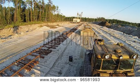 RUSSIA, VOSKRESENSK - JUL 1, 2014: Sandpit with excavator and bulldozers near railroad during sunset. Aerial view. Photo with noise from action camera.