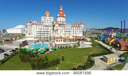 RUSSIA, SOCHI - JUL 29, 2014: Bogatyr hotel complex near amusement park at summer sunny day. Aerial view. Photo with noise from action camera.