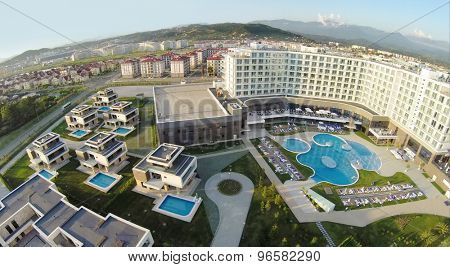 RUSSIA, SOCHI - JUL 25, 2014: Private apartments near common pool with people in hotel Radisson Blu at summer sunny day. Aerial view. Photo with noise from action camera