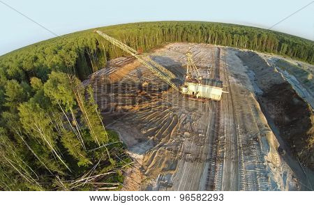 RUSSIA, VOSKRESENSK - JUL 1, 2014: Excavator ladles sand near forest during sunset. Aerial view. Photo with noise from action camera.