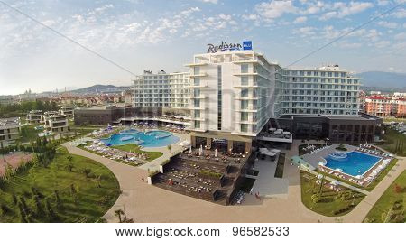RUSSIA, SOCHI - JUL 26, 2014: Edifice of Radisson Blu hotel with signboard on roof at summer day. Aerial view. Photo with noise from action camera.