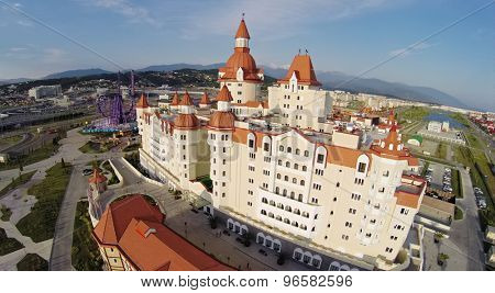 RUSSIA, SOCHI - JUL 27, 2014: Edifice of hotel Bogatyr near Sochi-park at summer sunny day. Aerial view. Photo with noise from action camera.