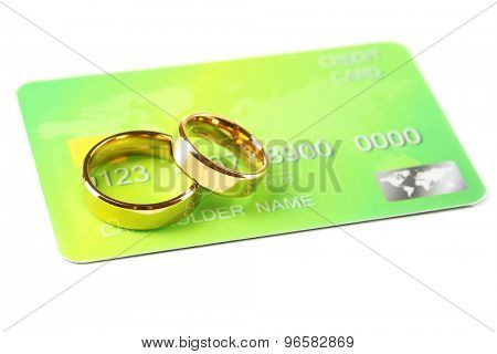 Golden wedding rings and credit card, isolated on white. Marriage of convenience concept