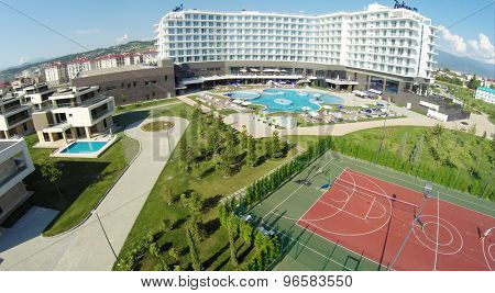 RUSSIA, SOCHI - JUL 25, 2014: Hotel Radisson Blu and tennis-court. Aerial view. Photo with noise from action camera.