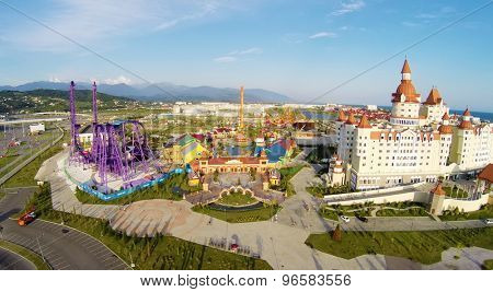 RUSSIA, SOCHI - JUL 27, 2014: Amusement park near hotel Bogatyr at summer sunny day. Aerial view. Photo with noise from action camera