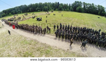 RUSSIA, NELIDOVO - JUL 12, 2014: Formation of soldiers in uniform of soviet and german armies during reconstruction Battlefield at sunny day. Aerial view. Photo with noise from action camera.
