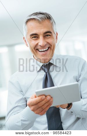Smiling Businessman Using A Digital Tablet