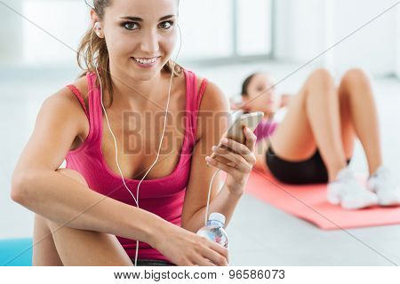 Young Woman Listening To Music At The Gym