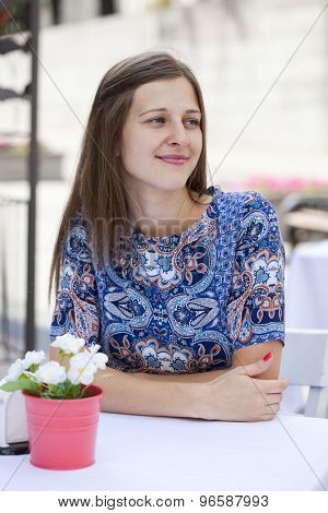 Young beautiful brunette girl sitting in a coffee shop