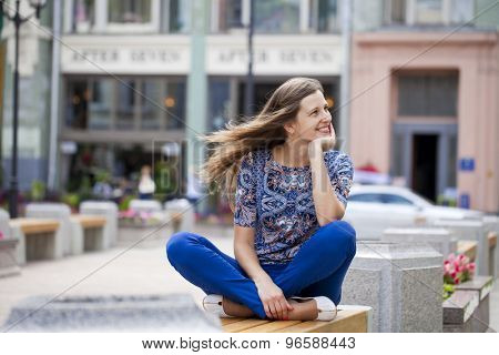 Happy Beautiful young woman sits on a bench in a summer street