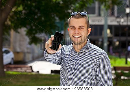 Happy young man shows a mobile phone screen in summer street