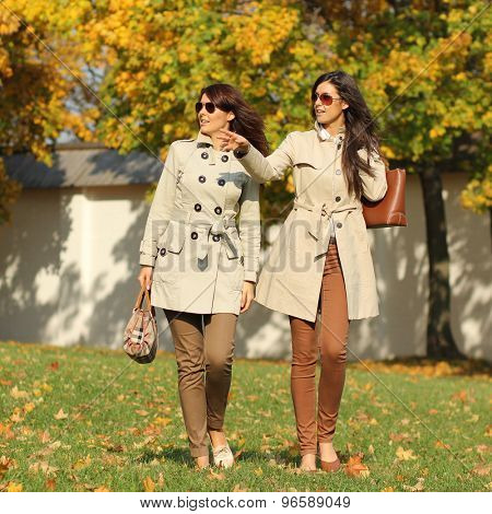 attractive women with autumn maple leaves in park at fall outdoors