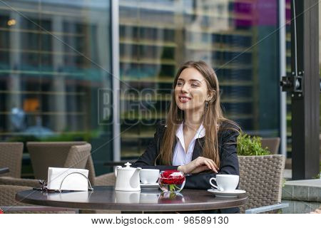 Young Business woman in drinking a cup of coffee in a summer cafe