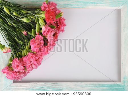 Beautiful bouquet of pink carnation with wooden frame isolated on white