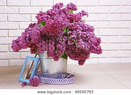 Beautiful lilac flowers in pail on floor in room close-up