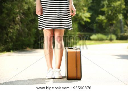 Young woman with vintage suitcase outdoors