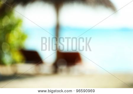 Sunbeds on beautiful beach in resort, blurred texture