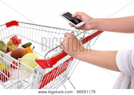Young woman holding mobile phone and shopping cart close up