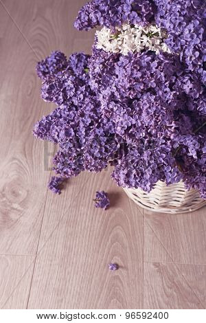 Beautiful lilac flowers in basket on wooden background
