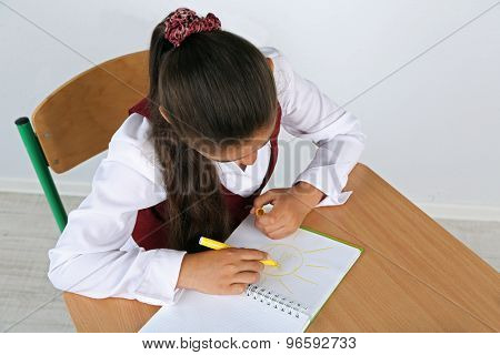 Beautiful little schoolgirl in classroom and draws in notebook
